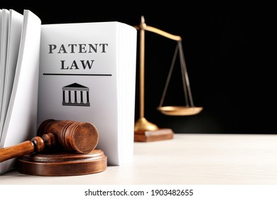 Judge's gavel, Patent Law book and scales on white table against black background. Space for text
