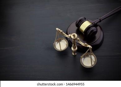 Die Richter schwingen und skalieren die Gerechtigkeit auf dem schwarzen Tischhintergrund. Rechtskonzept.