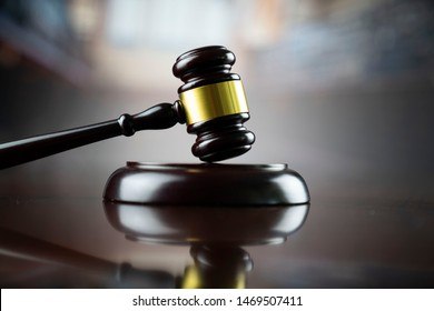 Judge's gavel, scales of justice, hourglass, books. Bokeh background.