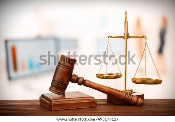 Judge's gavel and scales on blurred computers background