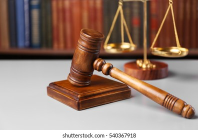 Judge's gavel with sound block and scales and books on background