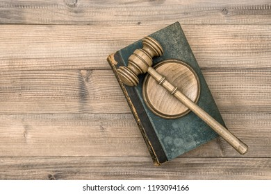 Judges gavel with soundboard and old book. Hammer on rustic wooden background