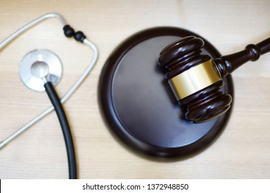 Judges gavel, sounding block and stethoscope on light wooden background, selective focus at sdf. Medical law system, health law, medical jurisprudence and justice concept.