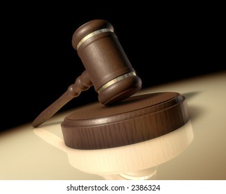A Judge's gavel in a spotlight on a reflective surface