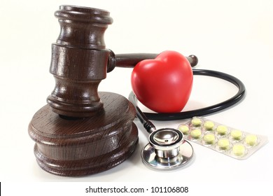 judges gavel with stethoscope and pills