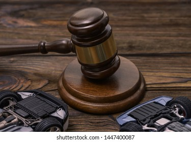 The judge's gavel, two upside-down car on wooden background. court decision.
