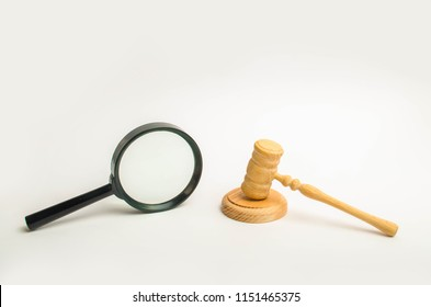 A judge's hammer and a magnifier on a white background. Acquaintance with the judicial case, research and evaluation of the effectiveness of the judicial system, the legality of the judicial decision.