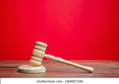 Judge's hammer on a red background. The judicial system. Norms, rules and laws. Conflict resolution in court. Court case, settling disputes. Protection of their rights and freedoms, honor. Gavel
