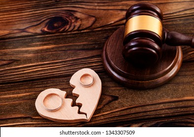 A judge's hammer, two halves of a heart, a pair of gold wedding rings on a wooden table background. family law.