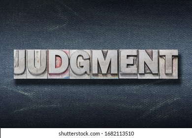 judgment word made from metallic letterpress on dark jeans background