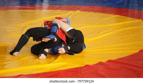 Judo, Jiu Jitsu, MAA, SAMBO. Two men are fighting on wrestling mat