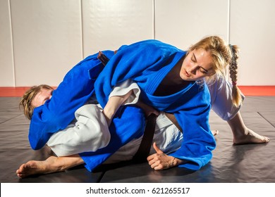 Judo, Jiu Jitsu. Two women are fighting on tatami. Blue and white kimano. Painful reception. Ground floor