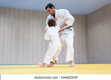 Judo kid and his trainer engaged in judo class in a dojo. Trainer teaches child the methods and techniques od ashi waza