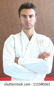 Judo practitioner standing on a mat with his arms folded