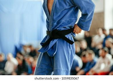 judoka blue kimono with black belt background spectators
