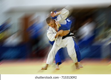Judoka in white judogi attempting to throw opponent in blue judogi with Sode Tsurikomi Goshi