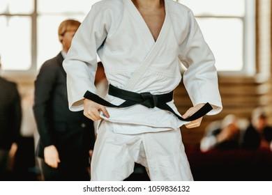judoka white kimono with black belt in background referee