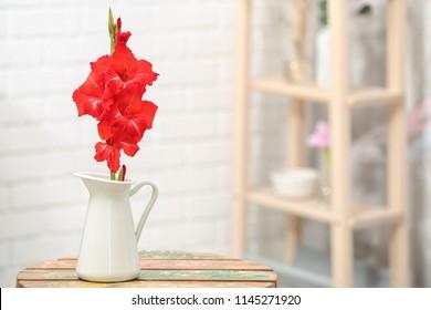 Jug with beautiful gladiolus flowers on table indoors