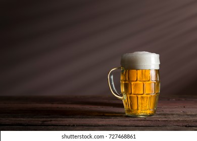 Jug of cold pale beer placed on a rustic wooden table