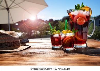Jug fresh cold summer drink on a sunny terrace with parasol and straw hat on wooden table. Background for vacation and leisure. Short depth of field.