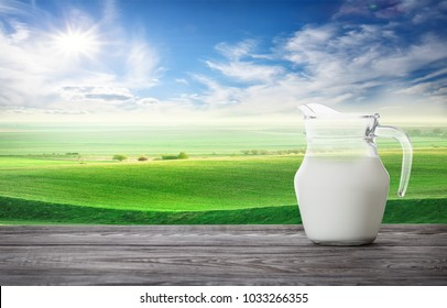 Jug of fresh milk against background of green wavy pasture