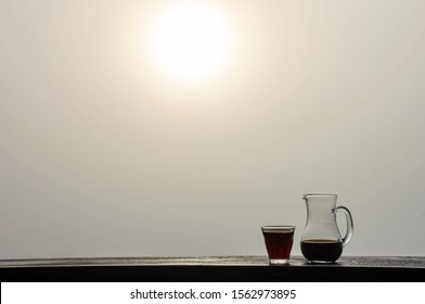 A jug and a glass of black coffee on a wooden table Background fog  and morning sunlight.