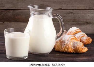 jug and glass of milk with croissants on a wooden background
