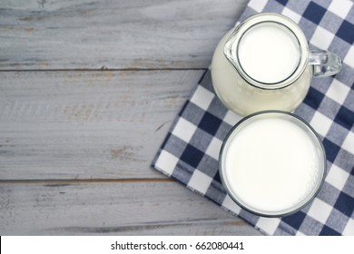 Jug and glass of milk on a wooden table, top view