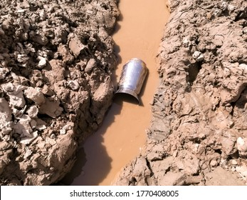 jug into dirty water in a drying pond cause of water crisis