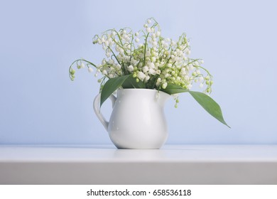 Jug with lily of the valley flowers bouquet