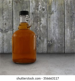 Jug of maple syrup in front of a weathered wood wall