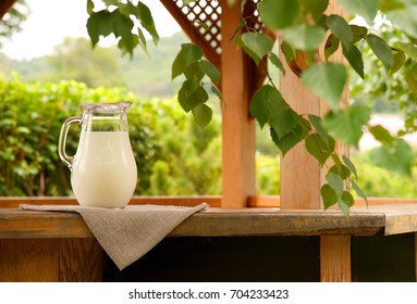 A jug of milk against the background of tree branches. Milk in a jug on the windowsill of the pergola. Jug of milk on a background of green tree leaves. Milk and rustic style. Country style.