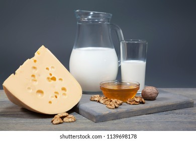 Jug with milk, cheese and honey on a wooden board. Composition isolated on gray background