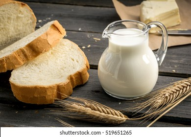 Jug of milk with freshly baked white bread and wheat ears