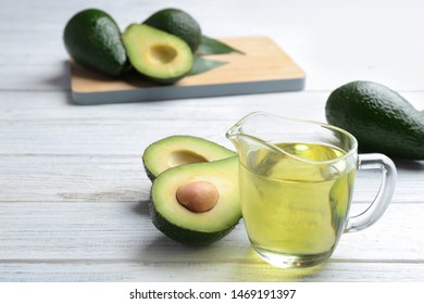Jug of natural oil and avocados on white wooden background. Space for text
