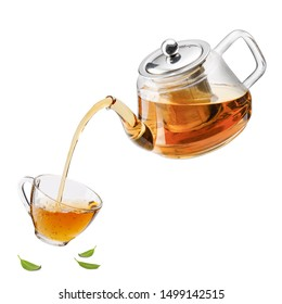 Jug pouring hot tea into glass cup with green tea leaves in the air, Healthy products by organic natural ingredients concept, Empty space in studio shot isolated on white background