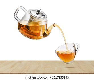 Jug pouring hot tea into glass cup with flying whirl green tea leaves in the air, Healthy products by organic natural ingredients concept, Empty space in studio shot isolated on white background