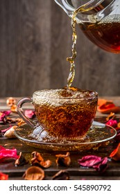 Jug of tea and cup stand on table with rose petals
