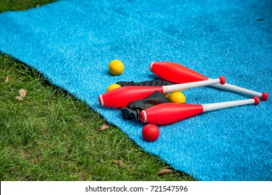 Juggling clubs and balls on lie blue mat close-up