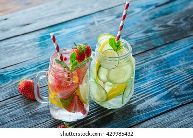 Jugs with lemon, lime and strawberry infused water on a rustic wooden table