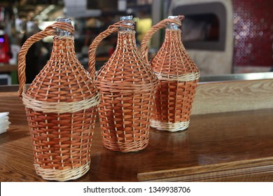 Jugs for wine with a wicker design on the table. Jugs for wine of different sizes. Wine jugs in a wicker design of grape vines.
