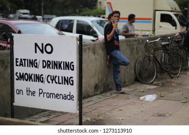 Juhu, Andheri, Mumbai, India - Jul-2012: People smoking, eating and cycling in spite of the signs suggesting otherwise.  No smoking, eating, drinking, cycling on Promenade