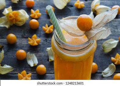 Juice of cape gooseberry in glass cup with scattered cape gooseberries on dark wooden background. Flat lay. Physalis