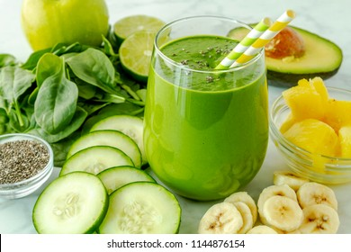 Juice glass filled with green kale and spinach smoothie with green and yellow swirl straws surrounded by ingredients sitting on marble counter