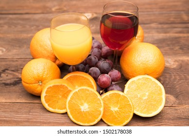 Juice glass and grape and orange fruit on wooden background