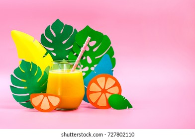 Juice in a grass with paper leaves and orange on side. Tropical concept. Selective focus.