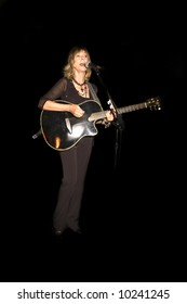 Juice Newton singing and playing guitar at a concert {for editorial use only}