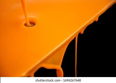 Juice, orange color flowing down surface into black background