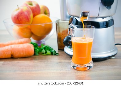 Juicer and carrot juice. Fruits in background