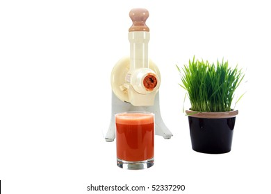 a juicer with carrot juice and wheat grass isolated on white